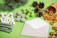 Weihnachtsgrußkarte mit Tannenzweigen, Geschenkboxen, Dekorationen, Ingwerplätzchen und Kiefernkegeln auf rustikalem Holztisch be lizenzfreie stockfotos