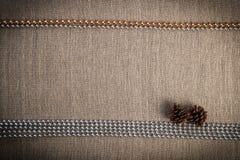 Weihnachtsgrußkarte mit zwei Kiefernkegeln und Silber-goldenen Perlen über Leinenhintergrund Lizenzfreie Stockfotos