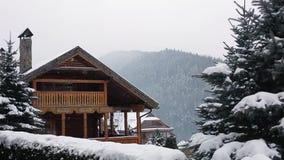 Weihnachtshölzerne Villa in den Bergen am Schneefallwintertag Gemütliches Chalet auf Skiort nahe Kiefernwaldhäuschen von stock video footage