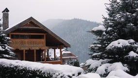 Weihnachtshölzerne Villa in den Bergen am Schneefallwintertag Gemütliches Chalet auf Skiort nahe Kiefernwaldhäuschen von stock video