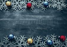Weihnachtshölzerner Hintergrund mit dekorativen Schneeflocken und Weihnachtsbällen Lizenzfreie Stockbilder