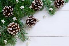 Weihnachtshölzerner Hintergrund mit Tannenzweigen und Kegeln Stockbilder