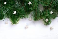 Weihnachtshölzerner Hintergrund mit Tannenzweigen und Sternen Stockfoto