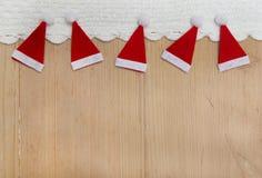 Weihnachtshüte, gewirkter Schnee auf hölzernem Hintergrund Lizenzfreies Stockbild