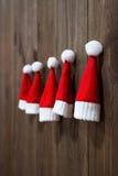 Weihnachtshüte von Weihnachtsmann Weihnachtsbaum spielt handgemachtes Zweig, Kasten, Handbell, Kugel Kleine Santa Claus-Hüte stockfotos
