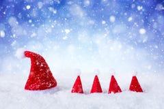 Weihnachtshüte vor Hintergrund der Schneeionenweißem blauen Sterne Stockfoto