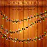 Weihnachtshauslichter auf einem hölzernen Hintergrund Lizenzfreie Stockfotografie