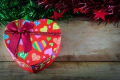 Weihnachtsherzgeschenkbox und -dekorationen auf hölzernem Lizenzfreies Stockbild