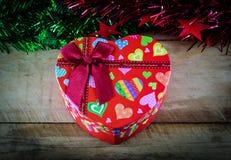 Weihnachtsherzgeschenkbox und -dekorationen auf hölzernem Stockbilder