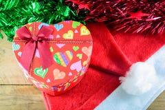 Weihnachtsherzgeschenkbox und -dekorationen auf hölzernem Stockfoto