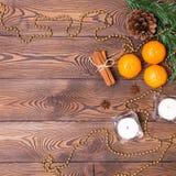 Weihnachtshintergrund - antikes Holz, Tannenzweige, Kiefernkegel, Kerzen und Tangerinen, der Dekor des neuen Jahres Flache Lage,  stockbild