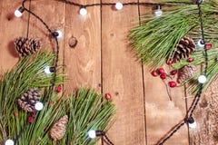 Weihnachtshintergrund auf altem hölzernem Brett mit Lichtern und Fichte Stockfoto