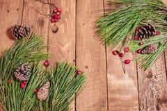 Weihnachtshintergrund auf alten Kegeln und Fichte des hölzernen Brettes Stockfotografie
