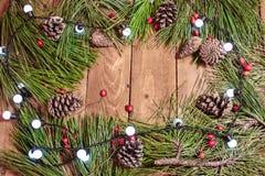 Weihnachtshintergrund auf roten berrys, Lichtern und Fichte des Weinleseholztischs Lizenzfreie Stockbilder