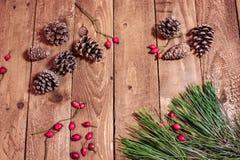 Weihnachtshintergrund auf roten berrys und Fichte der alten hölzernen Plattform Lizenzfreie Stockbilder