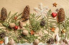 Weihnachtshintergrund des Sperrholzes mit Schokolade, Bälle, Kiefernkegel mit Schneeflocke auf den Niederlassungen eines Thuja Lizenzfreies Stockfoto
