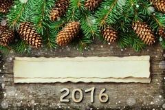 Weihnachtshintergrund des Tannenbaums und des Nadelbaumkegels auf hölzernem Brett der alten Weinlese, fantastischer Schneeeffekt, Stockfotografie