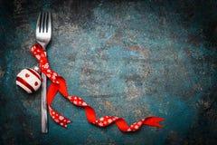Weihnachtshintergrund für festliches Abendessen mit Gabel und rote Dekoration auf Weinlesehintergrund Stockfoto
