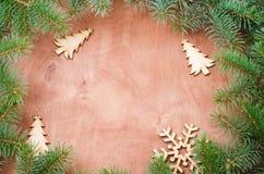 Weihnachtshintergrund für Weihnachtspostkarte Weihnachtsbaumaste mögen einen Rahmen auf hölzernem Hintergrund Platz für Text Stockbilder