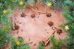Weihnachtshintergrund für Weihnachtspostkarte Zimtstangen, Anissterne und Nelken auf hölzernem Hintergrund Gezogener Schnee Stockbild