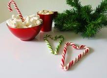 Weihnachtshintergrund, Grußkarte mit einem Tasse Kaffee oder einer Schokolade mit Eibischen, Zuckerstangen, eine rote Platte und  Lizenzfreies Stockfoto