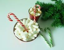 Weihnachtshintergrund, Grußkarte mit einem Tasse Kaffee oder einer Schokolade mit Eibischen, Zuckerstangen, eine rote Platte und  Stockfotos