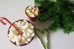Weihnachtshintergrund, Grußkarte mit einem Tasse Kaffee oder einer Schokolade mit Eibischen, Zuckerstangen, eine rote Platte und  Lizenzfreies Stockbild