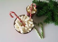 Weihnachtshintergrund, Grußkarte mit einem Tasse Kaffee oder einer Schokolade mit Eibischen, Zuckerstangen, eine rote Platte und  Stockfotografie