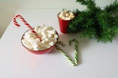 Weihnachtshintergrund, Grußkarte mit einem Tasse Kaffee oder einer Schokolade mit Eibischen, Zuckerstangen, eine rote Platte und  Lizenzfreie Stockfotos