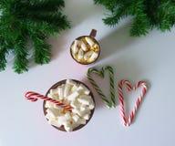 Weihnachtshintergrund, Grußkarte mit einem Tasse Kaffee oder Schokolade mit Eibischen, Lutschern, einer roten Platte und Baumaste Stockfotos