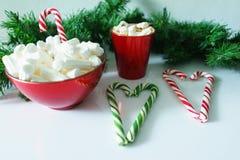 Weihnachtshintergrund, Grußkarte mit einem Tasse Kaffee oder Schokolade mit Eibischen, Lutschern, einer roten Platte und Baumaste Lizenzfreies Stockbild