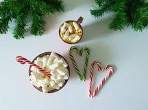 Weihnachtshintergrund, Grußkarte mit einem Tasse Kaffee oder Schokolade mit Eibischen, Lutschern, einer roten Platte und Baumaste Stockfotografie