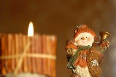 Weihnachtshintergrund, Kerze und lustiger Schneemann Stockfotografie