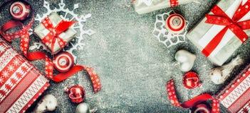 Weihnachtshintergrund mit Büttenpapierschneeflocken, Geschenkboxen und roten Dekorationen auf rustikalem Hintergrund, Draufsicht Stockfoto