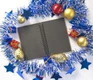 Weihnachtshintergrund mit blauem Laubbandkranz, Tannenbaumspielwaren, schwarzes Papier Stockbild