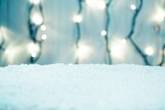 Weihnachtshintergrund mit bokeh einer leuchtenden Girlande und des Schnees Lizenzfreies Stockbild