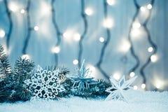 Weihnachtshintergrund mit bokeh einer leuchtenden Girlande und des Schnees Lizenzfreie Stockbilder