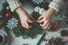 Weihnachtshintergrund mit den weiblichen Händen und den Dekorationen stockbild