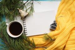 Weihnachtshintergrund mit einem Tasse Kaffee, einem Notizbuch, Niederlassungen der Kiefer mit großen Nadeln und einer gelben Stri Stockfoto