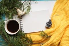 Weihnachtshintergrund mit einem Tasse Kaffee, einem Notizbuch, Niederlassungen der Kiefer mit großen Nadeln und einer gelben Stri Lizenzfreie Stockbilder