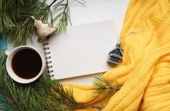 Weihnachtshintergrund mit einem Tasse Kaffee, einem Notizbuch, Niederlassungen der Kiefer mit großen Nadeln und einer gelben Stri Stockfotografie