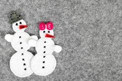 Weihnachtshintergrund mit Filzdekoration: Paare des Schneemannes Stockbild
