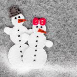 Weihnachtshintergrund mit Filzdekoration: Paare des Schneemannes Stockfotos