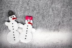 Weihnachtshintergrund mit Filzdekoration: Paare des Schneemannes Stockfoto