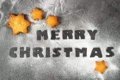 Weihnachtshintergrund mit gebackenen Lebkuchensternen und den Weihnachten der Wörter frohen gemacht vom Puderzucker Kreative Idee Lizenzfreie Stockfotos