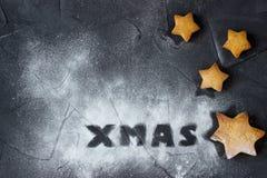 Weihnachtshintergrund mit gebackenen Lebkuchensternen und Wort Weihnachten gemacht vom Puderzucker Kreative Idee Stockfotografie