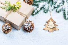 Weihnachtshintergrund mit Geschenk, Weihnachtsbaumasten, Schnee, Schneeflocke und Dekorationen Lizenzfreie Stockfotos