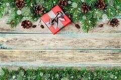 Weihnachtshintergrund mit Geschenkbox-, Tannenzweig- und Nadelbaumkegel auf hölzernem rustikalem Brett, festlicher Schneeeffekt,  Stockbild