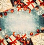 Weihnachtshintergrund mit Geschenkboxen, roten festlichen Feiertagsdekorationen und Papierschneeflocken Stockfotos