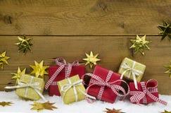 Weihnachtshintergrund mit Geschenken und Geschenken im Gold und im Rot Lizenzfreies Stockfoto